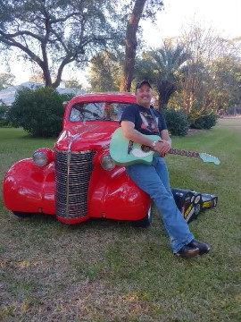 Music Performer, Jody Lucas relaxes with his guitar on beautiful antique car